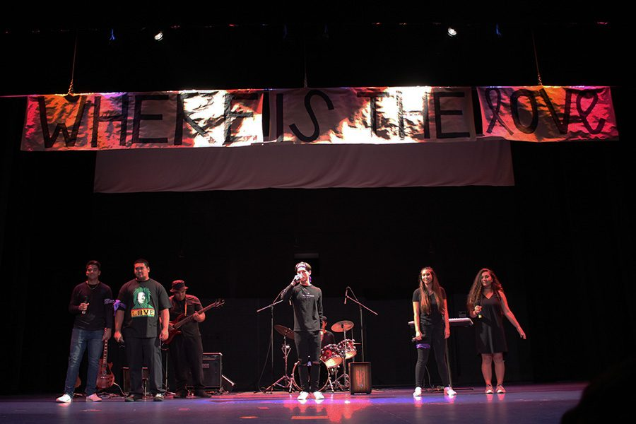 The+junior+band+sing+%22Where+is+the+Love%22+while+a+banner+slowly+descends+from+the+ceiling.+Their+performance+was+one+of+six+at+the+Monday+assembly+that+kicked+off+the+2017+Spring+Spirit+Week.