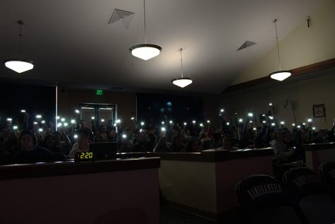 The juniors show class spirit by waving their cellphone lights back and forth during their song.