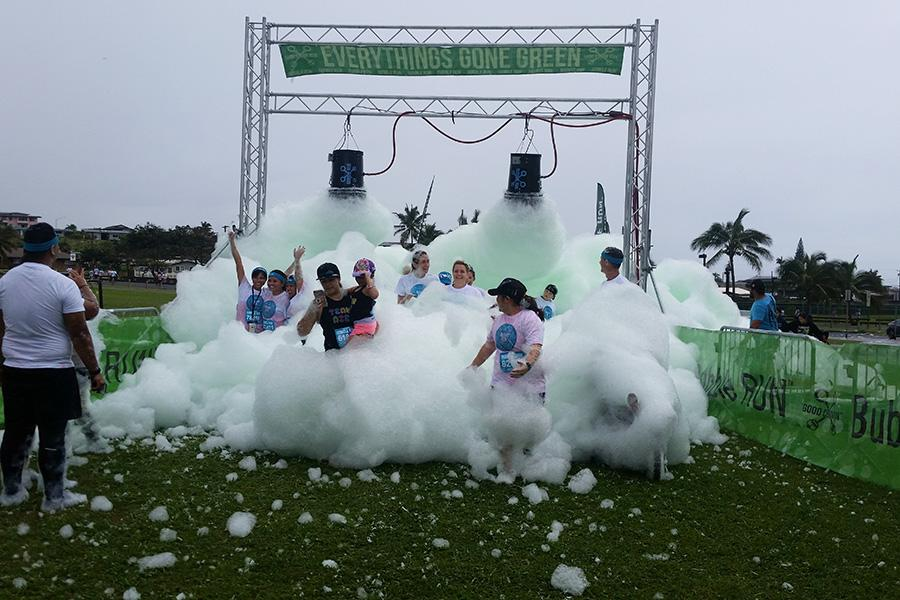 Green foam pours over runners at the Maui Bubble Run, Feb. 11, in Kahului.