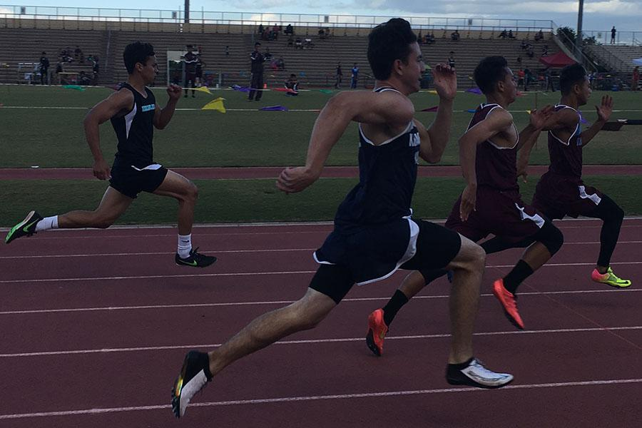 Junior Spencer Keanini competes in the boys 100-meter dash in the 5th track and field meet last night. Teammates and many family and friends cheered the athletes on as they ran. A few of the Warriors made the top eight in their event and competed in Saturday's finals as well.