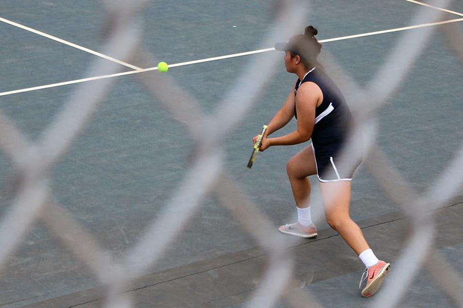 Junior Saje-Marie Pedroza-Kanemitsu hits with her backhand in Wednesday's match against King Kekaulike High School. The Warriors lost, 2-3, girls, and 0-5, boys.
