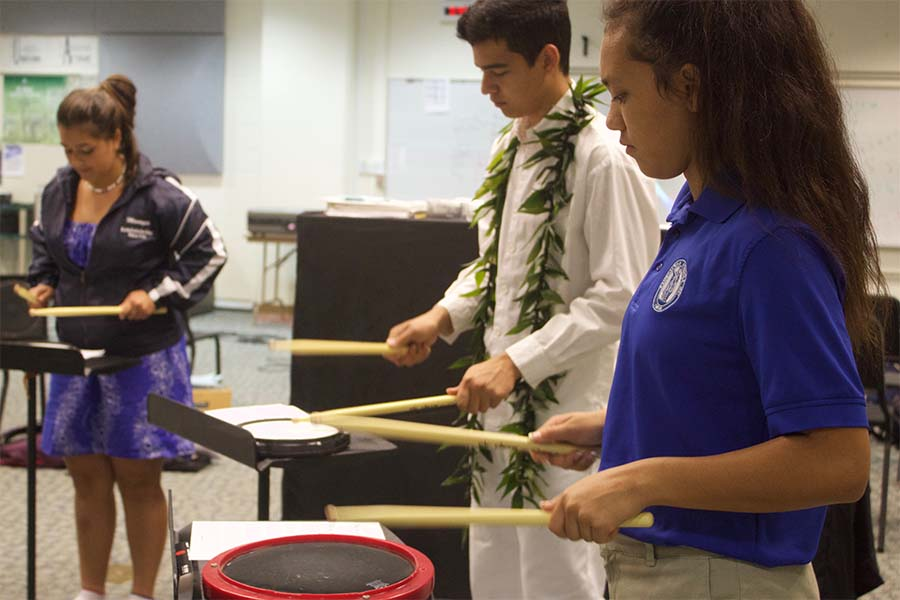 Sophomores Analicia Kapua, Christian Niles and freshman Tatiana Soon practice a drum beat Wednesday afternoon, April 12, in the High School Band Room with Ms. Kim and Mr. Jones. The Drumline had their first meeting with set practice schedules and audition dates.