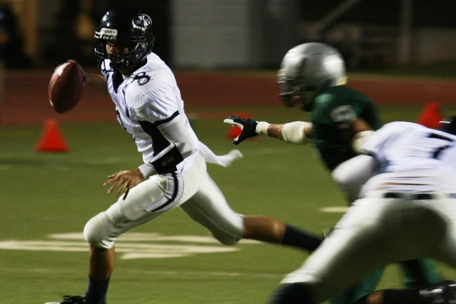 Quarterback Kala`i Yap runs a play while trying to avoid a tackle from Kapa`a during a pre-season game at Kana`iaupuni stadium on August 18, 2012. The KS Warriors lost 27-13.