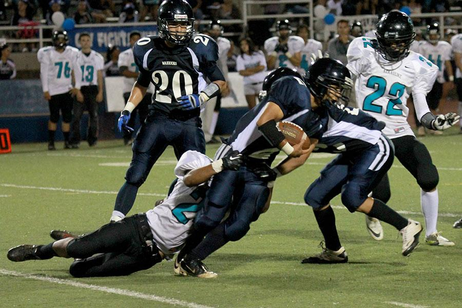 Kamehameha Maui's Chase Alexander runs while being tackled by Na Ali'i during their first 2013 MIL football game at Kana'iaupuni Stadium on Saturday, August 24, 2013. The Warriors won 29-0.
