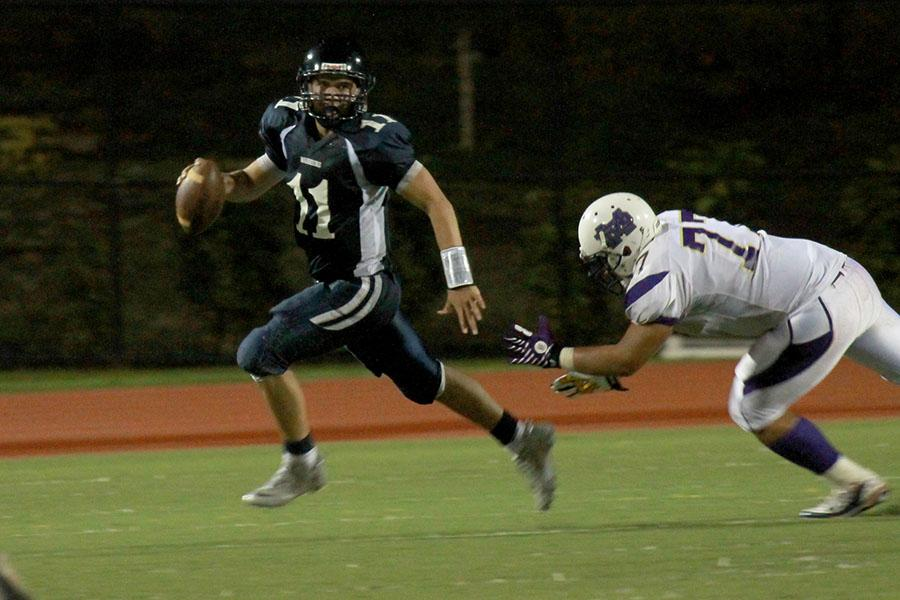 Quarterback Chase Newton runs and looks for a pass while being trailed by a Damien defender during a pre-season game at Kana'iaupuni Stadium on August 10, 2013. The KS Warriors lost 29-21.