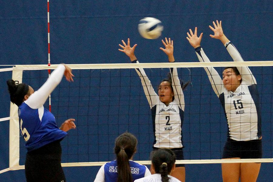 Victoria Kunishi and Patricia Batoon block a serve by the Sabers.