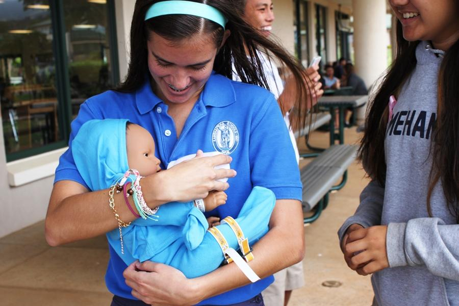 Sophomore Kasey Redman cares for her baby by feeding it with a bottle that comes with the RealCare® Baby Simulator. This years sophomores have an all-new program to use for this years baby project.