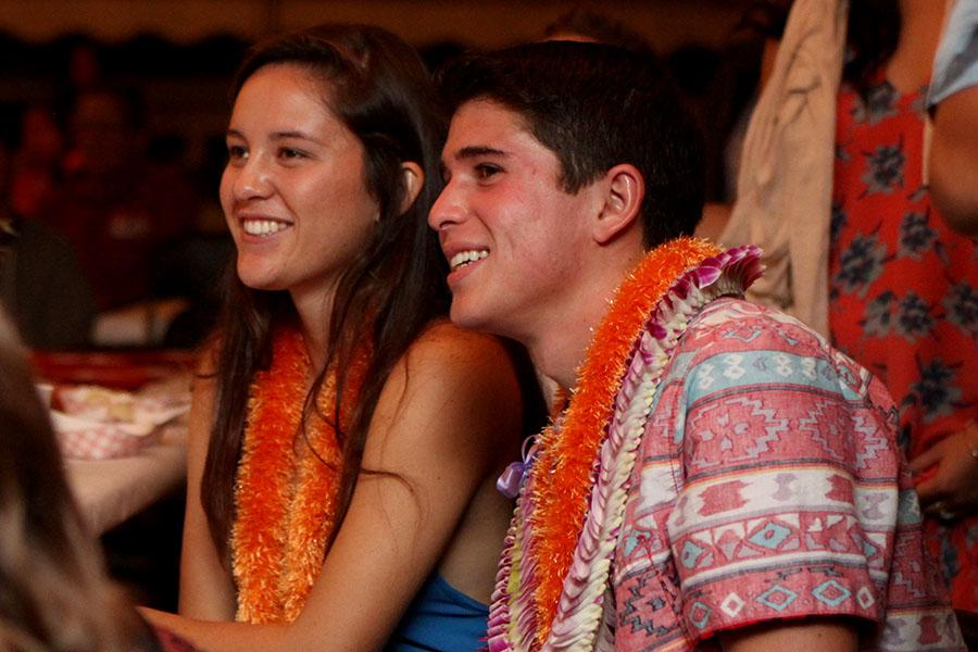 Seniors Lily Higashino and Chandler Alo enjoy the slideshow presentation made by Ciana Ruidas last night, November 16, on the high school quad. They are also wearing lei donated by the Yamamoto family.