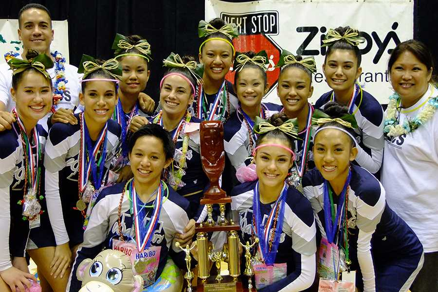 The Kamehameha Schools Maui varsity cheerleaders show off their state championship trophy with coaches Ann Saffery and Kealii Molina at the Neil Blaisdell Arena, Nov. 17, 2013.