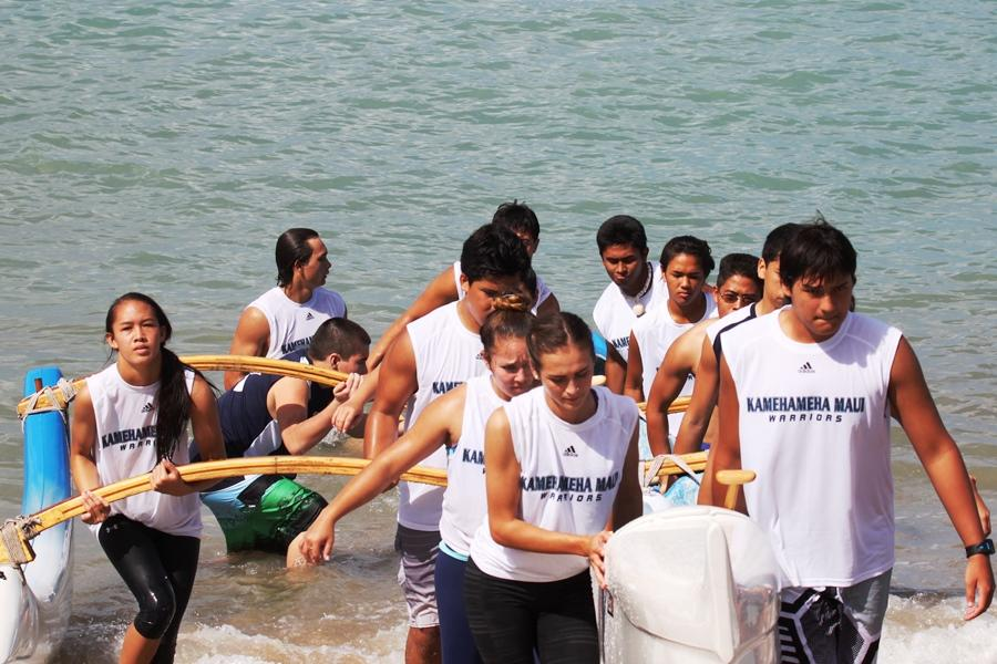 The+varsity+team+works+together+to+carry+up+the+canoe+at+MIL+Paddling+Meet+%233+at+Kahului+Harbor+on+Saturday%2C+January+11%2C+2014.