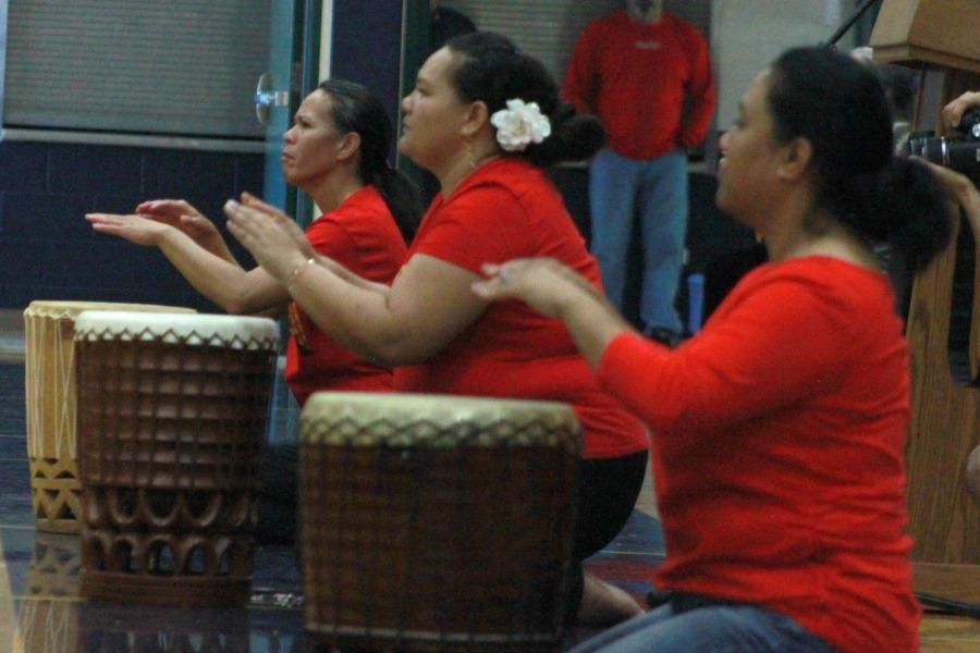 Nā Kumu Kuʻulei Alcomindras-Palakiko, Henohea Kane, and Kalei Aarona-Lorenzo on the pahu.