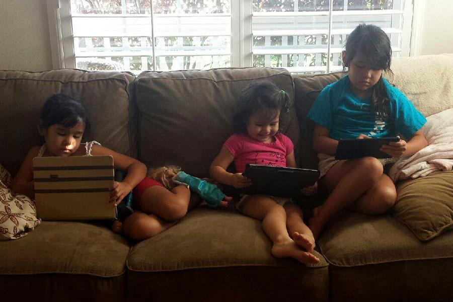 Ava (4), Mailah,(2) and Chloe (6) Cuomo of Kīhei, sit at home after school playing on their iPads, while a more traditional toy, a Barbie doll, waits nearby.