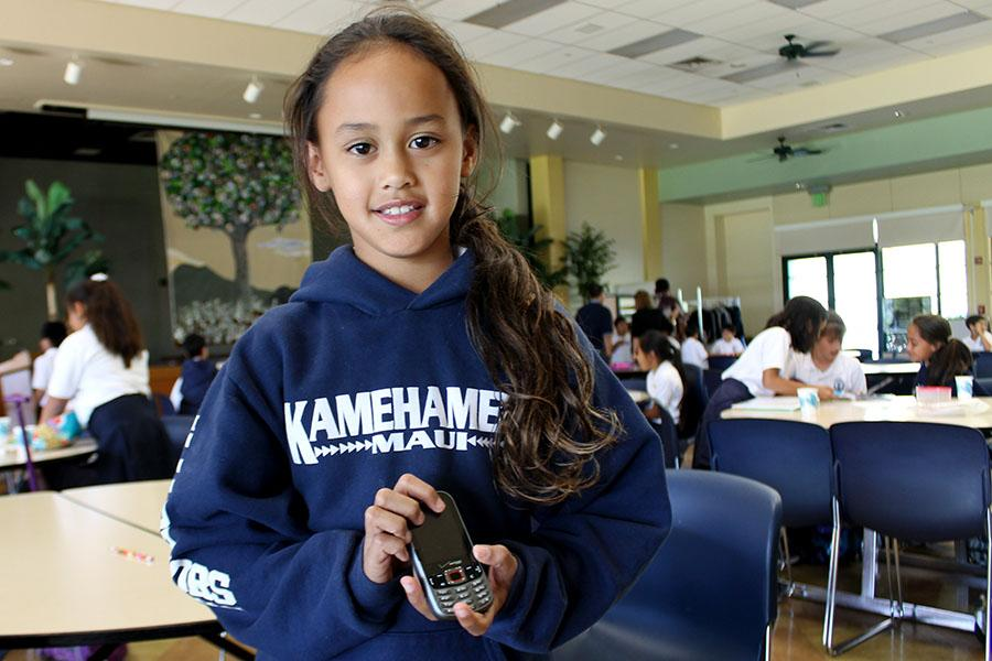 Lahikina Artates, a second grader at Kamehameha Schools Maui, shows off her cellphone. As a member of Generation Z, she and her classmates accept generation innately, creating concerns among their parents.