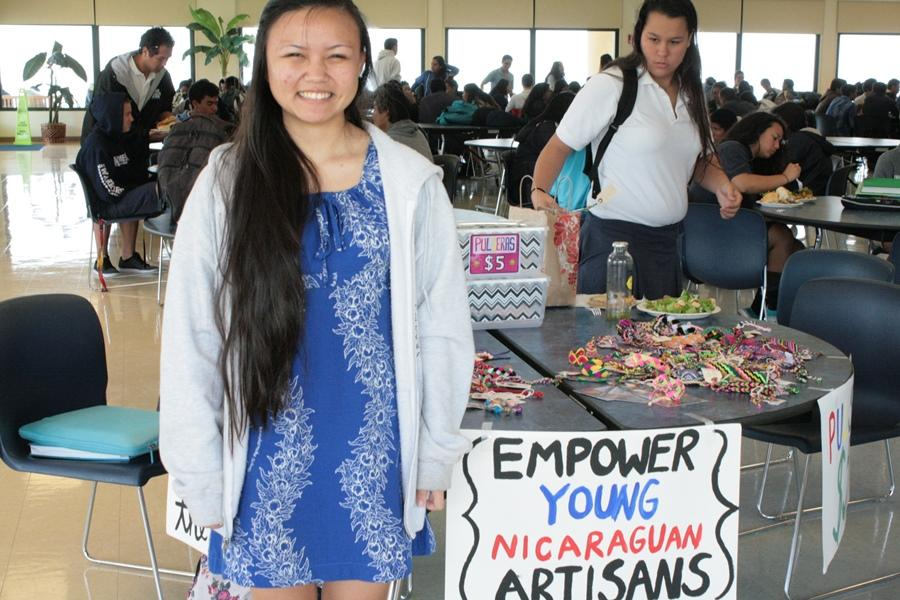 Junior Carolynn Krueger stands beside her Pulsera Project booth. Students can buy pulseras, or woven bracelets, until this Friday, May 2. The proceeds help Nicaraguan artists.
