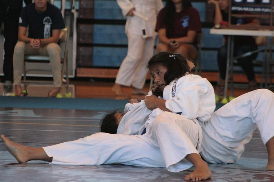 Senior Neʻula Aarona pins her opponent during the judo matches on April 26, 2014. Aarona won first place in her 154-lb. weight class.