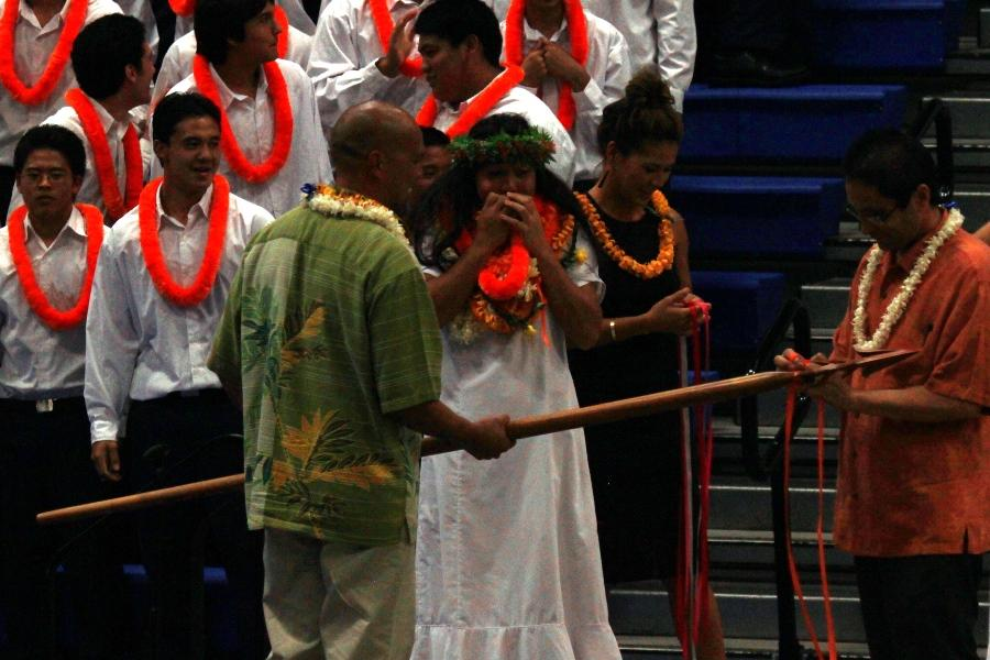 Senior song leader watches in wonderment as Vice Principal Leo Delatori ties the seniors' orange ribbon onto Ka Maka o Ka Ihe after the announcement of the class of 2014 win at 'Aha Mele, April 17.