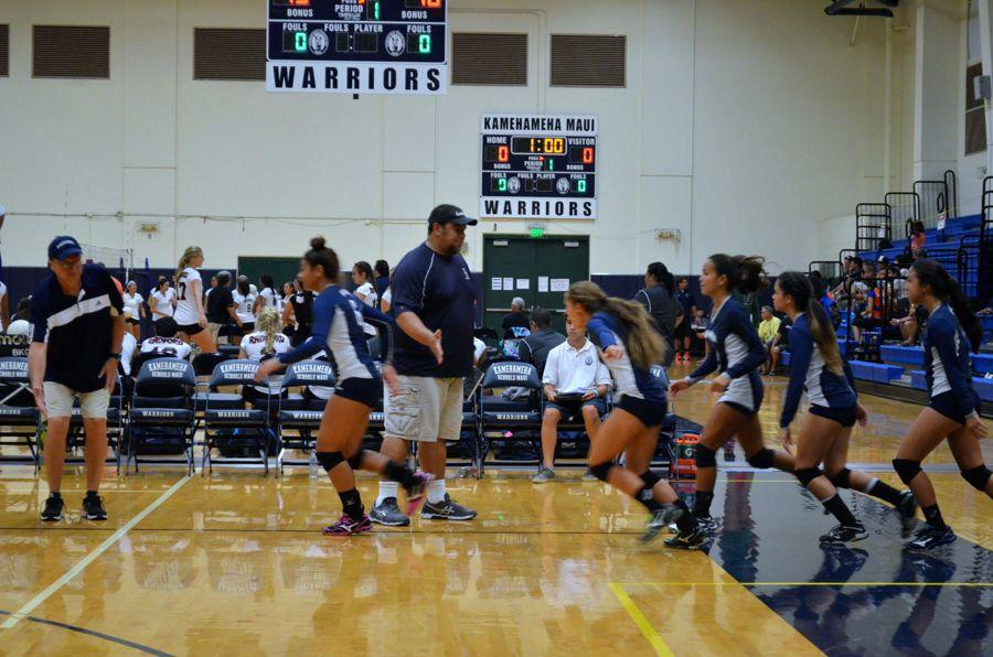 Coach Bala Spencer wishes luck to the varsity girls before Friday night's third set against Castle High School. The Warriors won the set 15-13, breaking a tie and winning their first game of the 5th Annual Kamehameha Maui Volleyball Invitational Tournament.