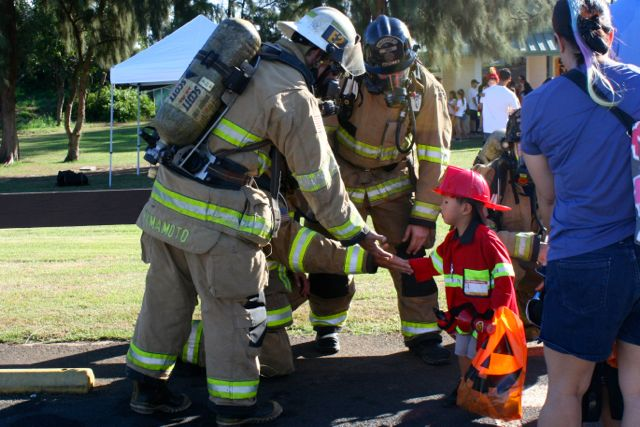 Small meets big as firefighters from the Maui Fire Department give high fives at the end of the walk.