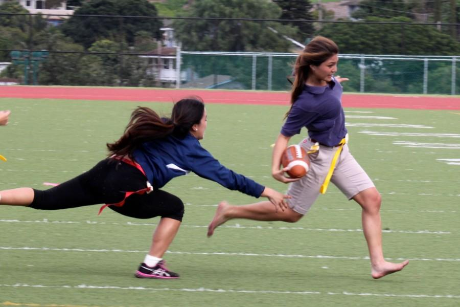 Sophomore Leialoha Medeiros maneuvers her way around opponent Junior Shayna Tamanaha at the powder puff football game Wednesday, December 17, at Kana'iaupuni Stadium. Medeiros made one touchdown, contributing to the yellow team's win, 13-12.