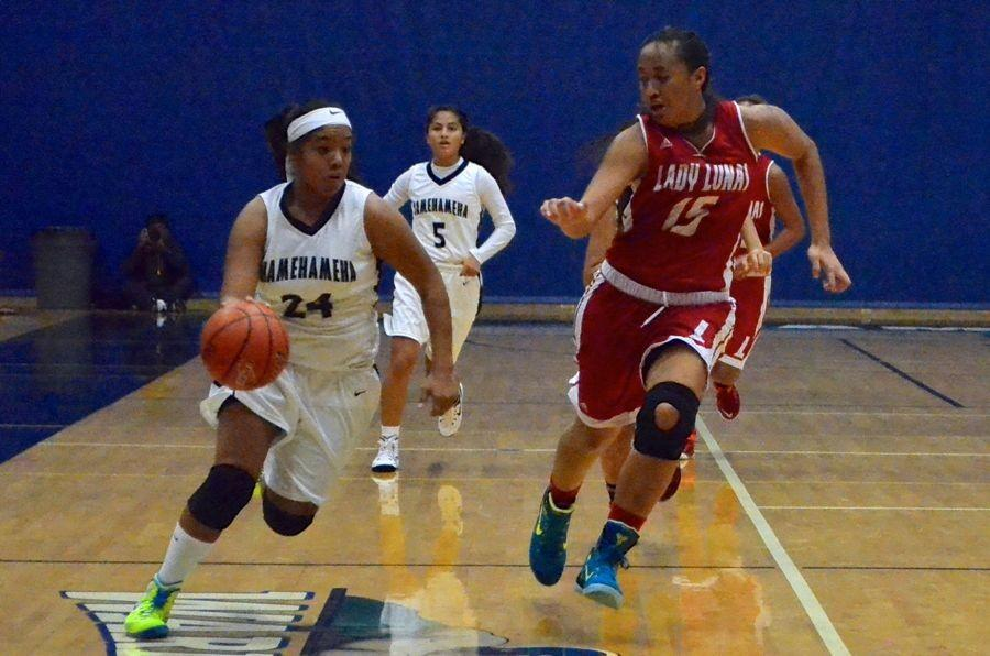 Freshman Ashley Peralta takes the ball down the court with Keleah Akio-Koloi in hot pursuit. Akio-Koloi was a high scorer in in last night's girls basketball game against the Maui Warriors in their regular season opener in Kaʻulaheanuiokamoku Gym. The Lunas won 73-20.