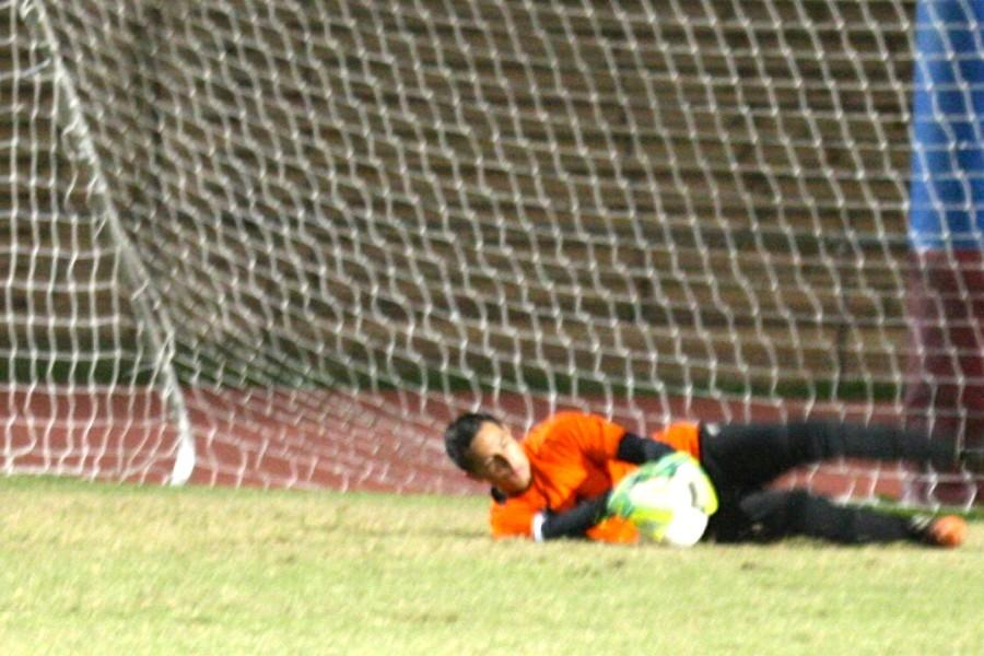 Keola Paredes makes a sliding save in the Warriors' second-round match against the Baldwin Bears, Tuesday, January 13, at War Memorial Stadium. The game ended in a 1-1 tie, keeping the Warriors in the lead by the slimmest of margins in the Maui Interscholastic League.