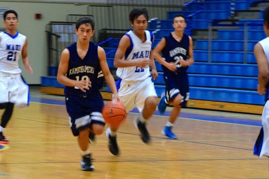 Freshman+Kalani+Gregory+dribbles+the+ball+down+the+court.