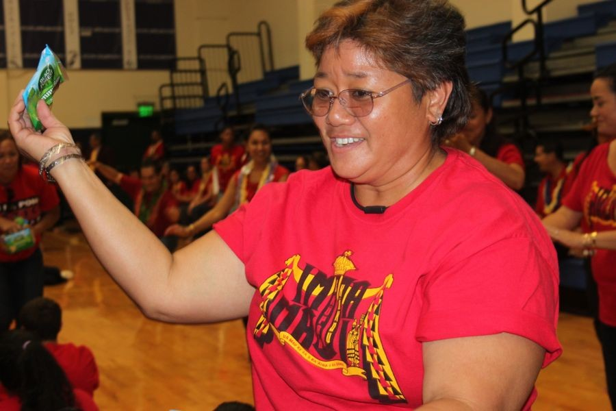 Educational assistant substitute Ms. Joella Taguchi hands out gummy snacks to students as a Red Friday treat.