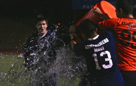 Micah Alo smiles as Daryn Nakagawa and Keola Paredes dump water on Coach Kyle Herendeen to celebrate their final win at War Memorial Stadium February 6, 2014. The Warriors defeated the Lunas and ended their season as league champions with two ties and no losses.