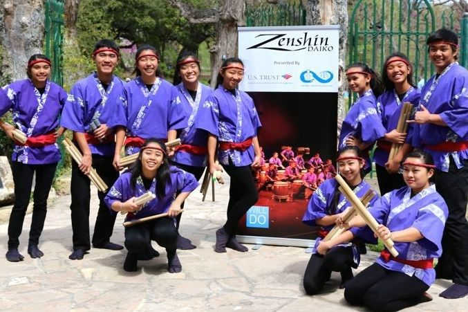 The 11 members of Maui's Zenshin Daiko pose in front of a poster advertising their upcoming performance at the San Antonio Country Club. The drum group went to Texas in March to perform at various venues, including the Will Smith Foundation Gala on March 19.