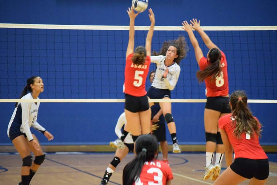 Luna Julia Bianco (7) covers Agust Guest (5) and Keolani Hill (4) as they attempt to block KSM Warrior Talia Leauanae (6) as she goes for the point in Friday night's game.