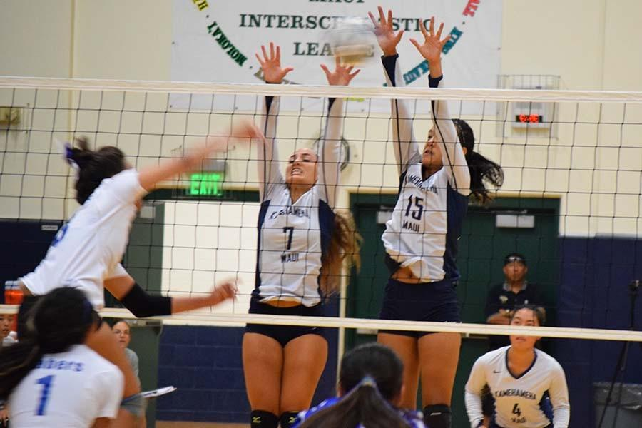 Danielle Brown (7) and Caylee Tuzon (15) block a spike from a Maui High Saber during Saturday nights game at Ka'ulaheanuiokamoku gymnasium. The Warriors came out on top with a score of 3-0.