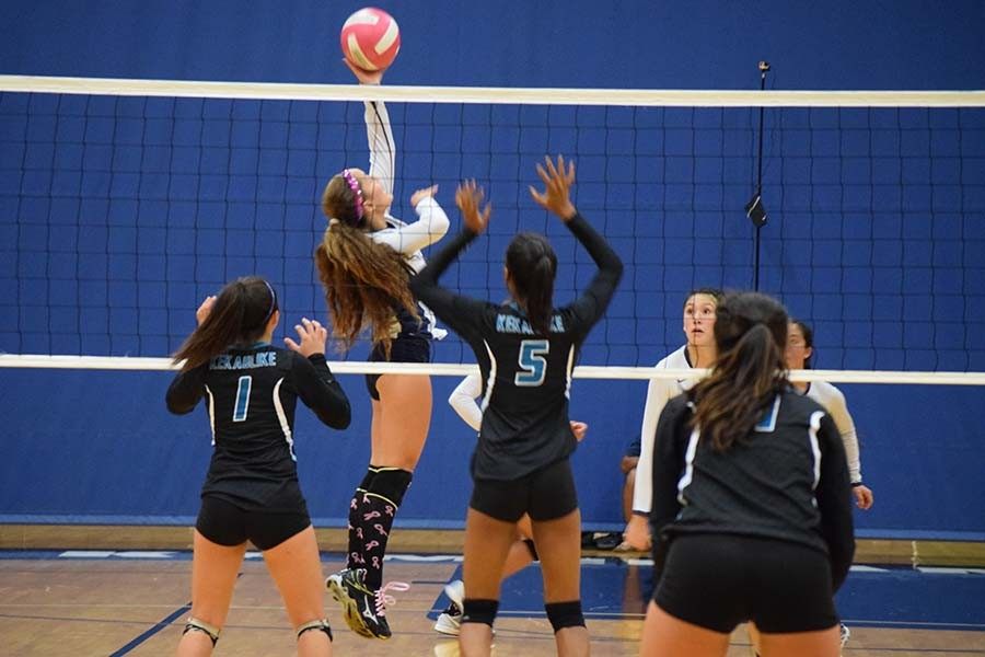 Danielle Brown (7) pushes the ball over the net as Nā Ali'i Treyanna-Lee Freitas (1) and Rose Love (5) get ready to save during the Dig Pink match on Friday, Sept. 18. The Warriors emerged victorious from the match with a score of 3-1.