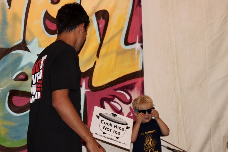 Kekoa Ostermiller outfits a young fair goer with an anti-meth sign for a photo op during his shift at the Hawaiʻi Meth Project booth at the 93rd Maui Fair, which ran Sept. 24-27.