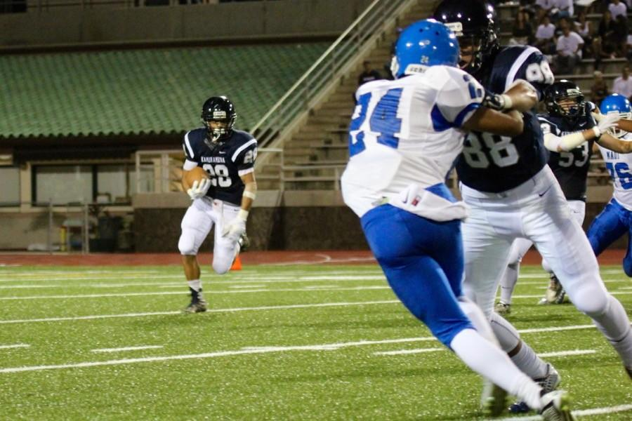 Sophomore Damon Martin runs the ball as Kealaula Keliikoa blocks Maui High's Kainoa Davis at the Warrior homecoming game in Kana'iaupuni Stadium on September 19, 2015. The Sabers won, 9-0, in front of a spirited Kamehameha crowd.