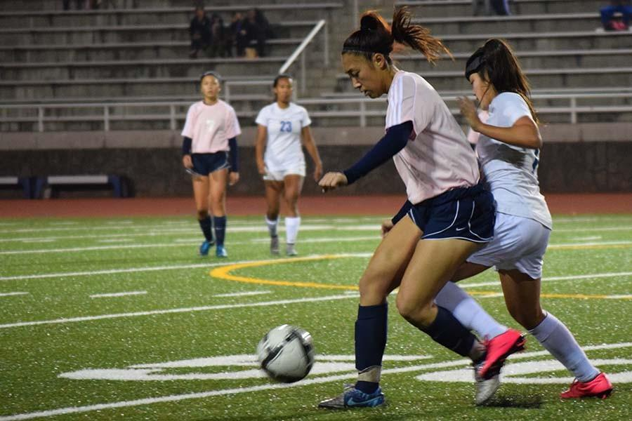 Ilihia Keawekane (10) and Jordyn Pa'a (11) fight for the ball in Tuesday night's game. It was also Senior Night for the Warriors and they showed they're pride by coming out on top with a score of 3-2 against the Maui High Sabers.