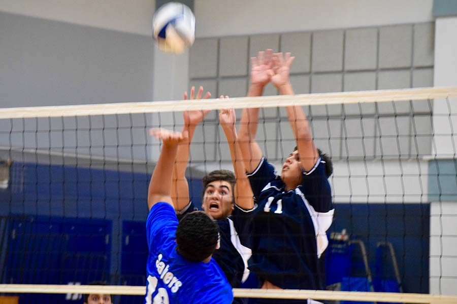 Kea Aguirre (10) and Brendan Urayanza (13) successfully block a spike. The Warriors beat the Maui High Sabers 2-1 in the match, April 20.
