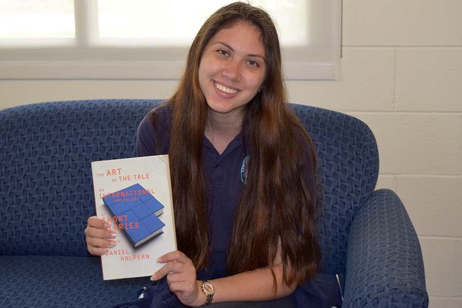 Senior Faith Owan poses with her Creative Writing II textbook titled