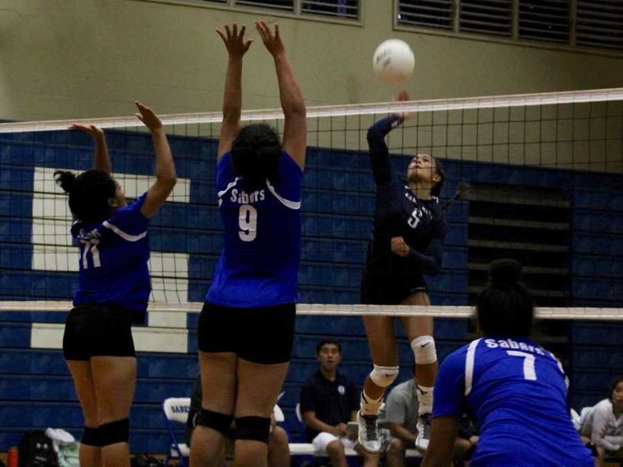Junior Aliah Ayau spikes the ball past three Sabers during the fourth and final set at the Maui High Gymnasium Thursday, Sept. 1. The Warriors won the match-up, 3-1.