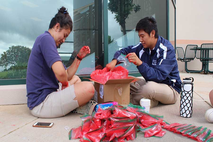 Quinn Shiraishi and Taylor Ching pack bags of color for the color run.