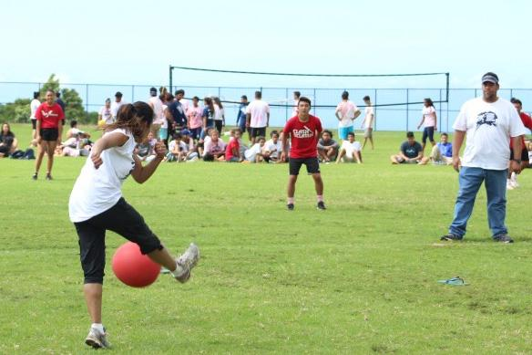 Ms. Helm goes for the kick as the seniors stand ready to react in the friendly kumu versus seniors game, Friday, Sept. 23. It was the final game in a weeklong kickball tournament that was part of homecoming activities leading up to the football game Friday night.