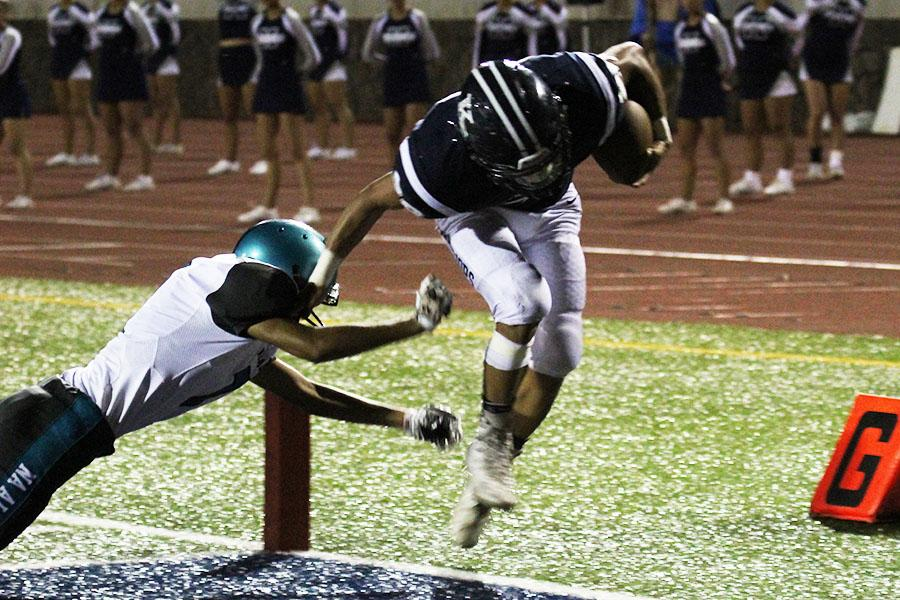 Damon Martin (#28) gallops over a Nā Aliʻi defender and into the end zone for his second rushing touchdown during the first half of the Kamehameha Maui homecoming game against King Kekaulike, Sept. 23, at Kana'iaupuni Stadium. The Warriors won 38-0.