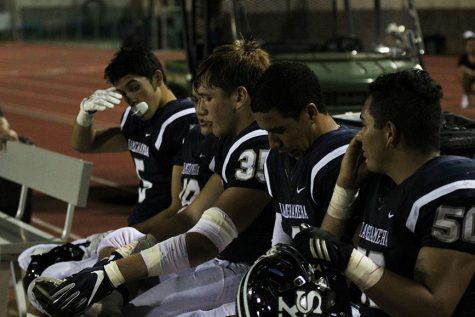Kamehameha Maui Warriors take a break on the bench while waiting for an injured member of Nā Aliʻi to be tended to.