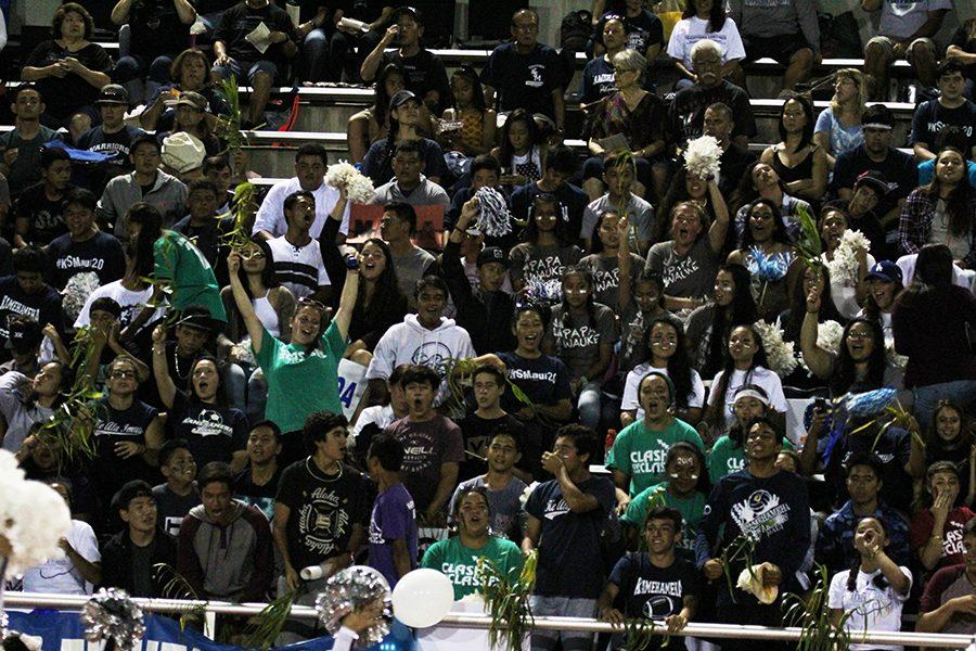 High school students sit together to cheer on the varsity football team during Friday night's football game.