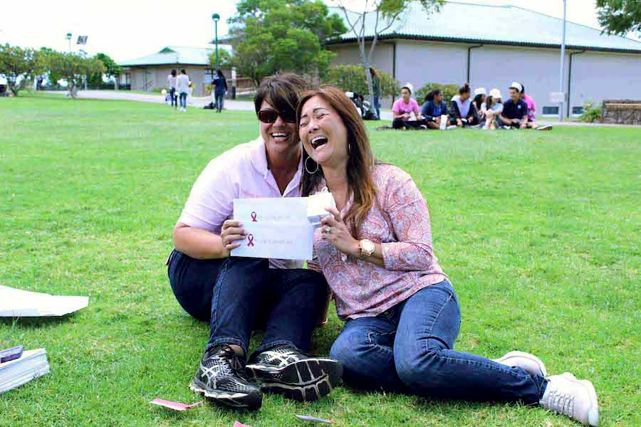 Athletic utility worker Ms. Tanya Souza and administrative assistant Ms. Ronnelle Suda laugh about their luck of winning four lottery prizes.