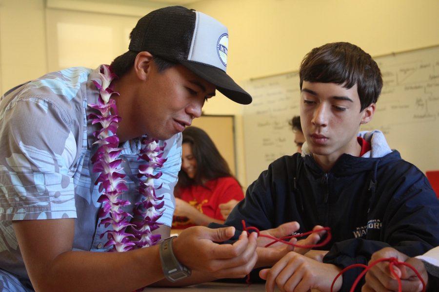 Alumnus Maleko Lorenzo teaches freshman Gabriel Arcas how to tie various knots he uses when voyaging on the Hokuleʻa.