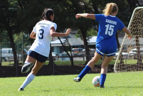 Sophomore Keely Logan dribbles past a Saber defender while also looking to shoot.