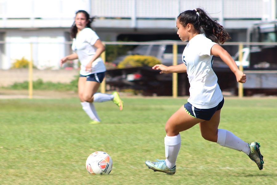 Freshman Kana Mateaki of Kamehameha Schools Maui dribbles down the field in a 4-1 victory over the Sabers of Maui High Saturday, Nov. 19. Spectators filled the bleachers and enjoyed a long and entertaining battle between the teams.