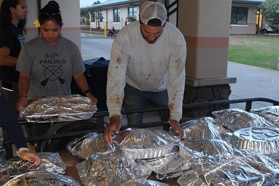 Staff from Puʻu Kukui Watershed, ʻohana and haumāna at Kamehameha Schools Maui prepare turkeys Wednesday night to put into nā imu behind Charles Reed Bishop Learning Center.