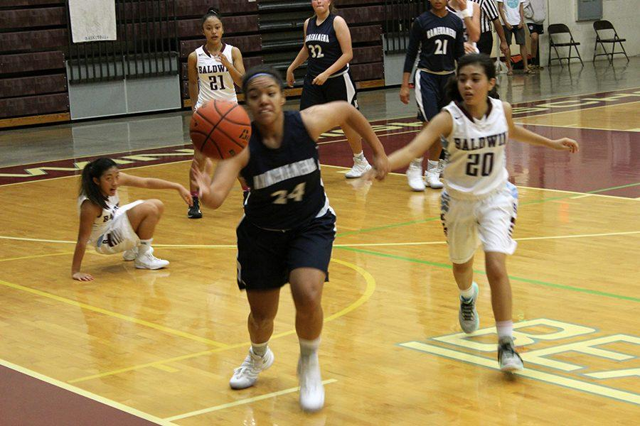 Ashley Peralta chases the ball in the match against the Baldwin Bears, Dec. 28, at Jon E. Garcia Gymnasium. The Warriors won 51-32.