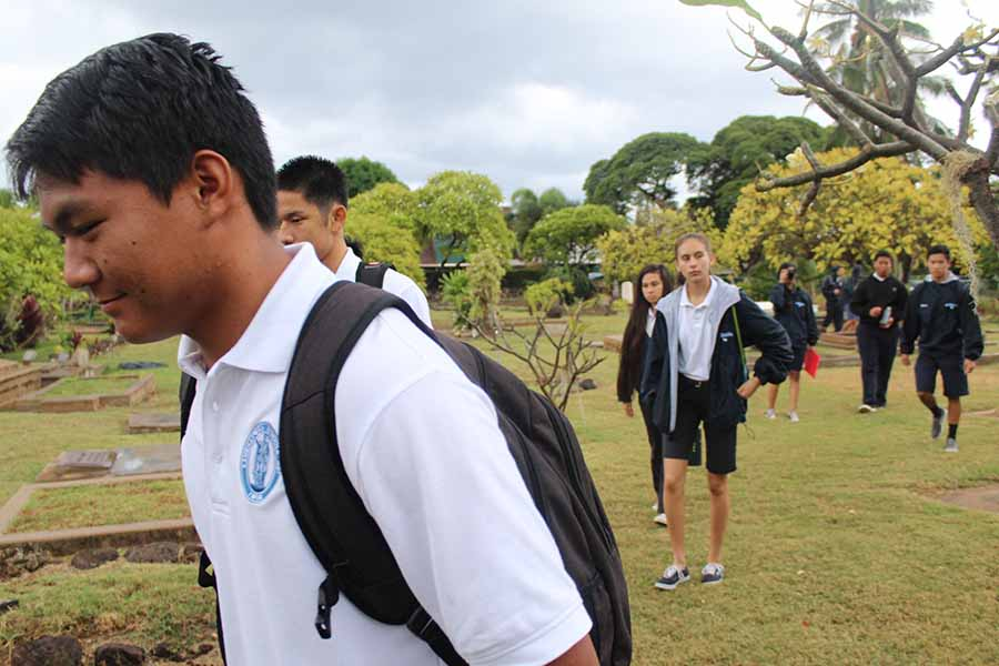 Sophomore Dane Abarra walks through the cemetery at Waiola Congregational Church on the trip to Lahaina with other Hawaiian classes.